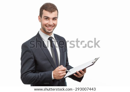 Portrait of a handsome young bearded man wearing a formal black suit holding a paper holder and a pen looking at the camera smiling, isolated on white background - stock photo