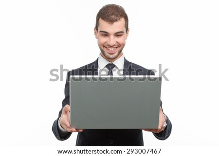 Portrait of a handsome young bearded man wearing a formal black suit standing and holding a laptop looking at it and smiling, isolated on white background - stock photo