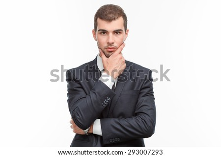 Portrait of a handsome young bearded man wearing a formal black suit standing looking serious and holding his hand on his chin, isolated on white background - stock photo