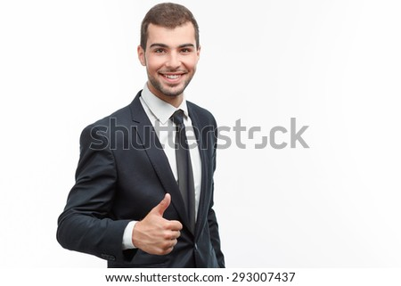 Portrait of a handsome young bearded man wearing a formal black suit standing smiling and showing thumb up, isolated on white background - stock photo
