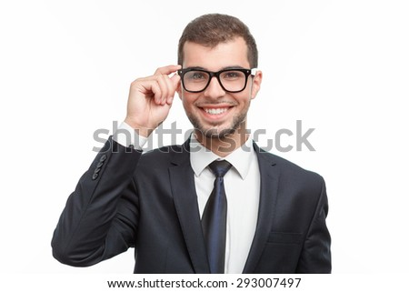 Portrait of a handsome young bearded man wearing a formal black suit touching his glasses and smiling, isolated on white background - stock photo