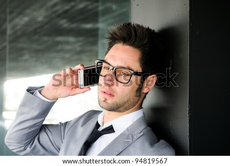 Portrait of a handsome young business man talking on mobile phone - stock photo