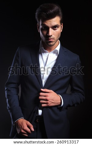 Portrait of a handsome young business man unbuttoning his jacket while looking at the camera. - stock photo