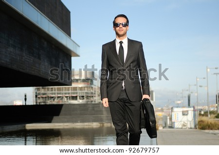 Portrait of a handsome young business man walking in the street - stock photo