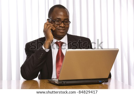 Portrait of a handsome young business man with a laptop and using mobile phone isolated - stock photo
