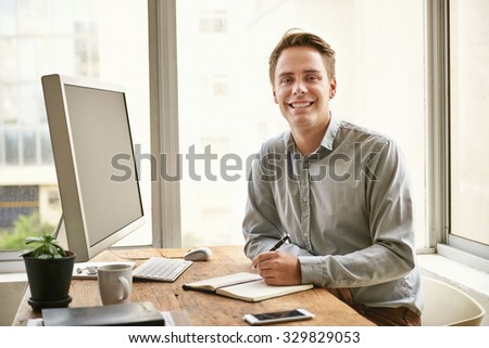 Portrait of a handsome young businessman sitting at his desk in a bright contemporary office space smiling confidently - stock photo