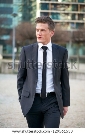 Portrait of a handsome young businessman walking outdoors - stock photo