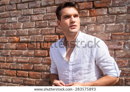 Portrait of a handsome young fashion man leaning on a brick wall while looking away from the camera. - stock photo