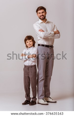 Portrait of a handsome young father and his cute little son standing back to back, looking in camera and smiling. Both in white classical shirts and gray pants, standing on a gray background. - stock photo