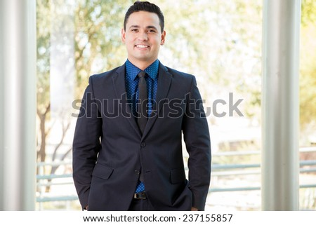Portrait of a handsome young Hispanic businessman smiling at work - stock photo