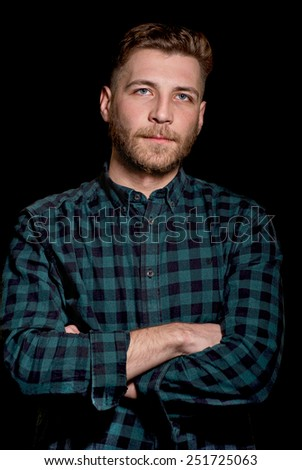 Portrait of a handsome young lumbersexual man on dark background - stock photo