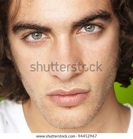portrait of a handsome young man against a green background - stock photo