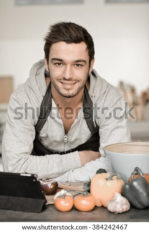Portrait of a handsome young man cooking with digital tablet in kitchen - stock photo
