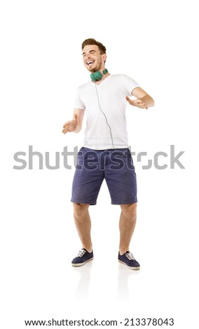 Portrait of a handsome young man dancing and listening music, isolated on white background - stock photo