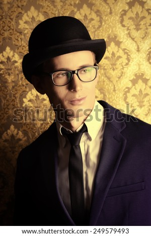 Portrait of a handsome young man in elegant suit and bowler hat posing over vintage background.  - stock photo