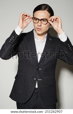 Portrait of a handsome young man in studio on a white background in a suit and glasses - stock photo