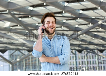 Portrait of a handsome young man laughing and talking on mobile phone - stock photo