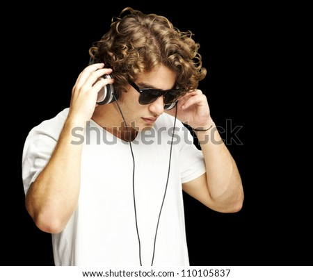 portrait of a handsome young man listening music against a black background - stock photo
