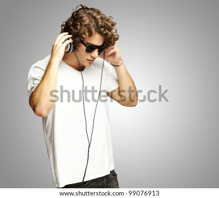 portrait of a handsome young man listening music against a grey background - stock photo