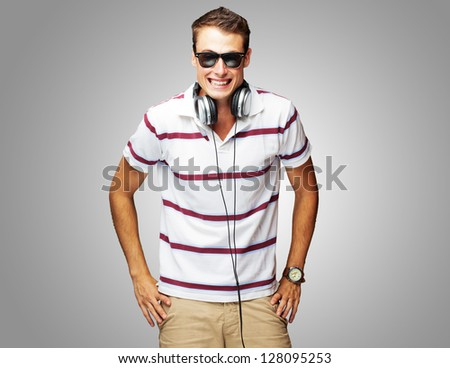 Portrait Of A Handsome Young Man Listening To Music On Gray Background - stock photo