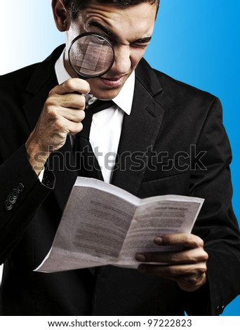 portrait of a handsome young man looking at a contract against a blue background - stock photo