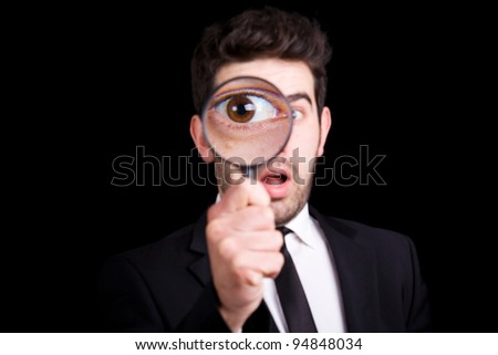 Portrait of a handsome young man looking through a magnifying glass against a black background - stock photo