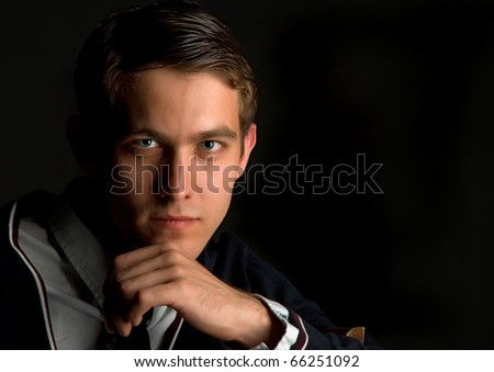 Portrait of a handsome young man on black background. - stock photo
