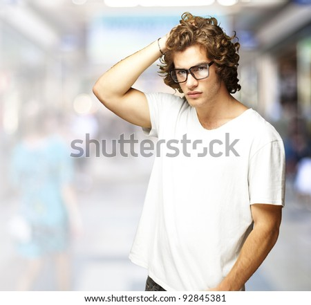 portrait of a handsome young man posing at a crowded place - stock photo