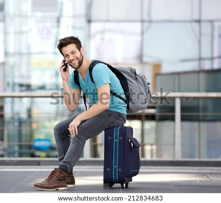 Portrait of a handsome young man sitting on suitcase and calling by cellphone at airport - stock photo