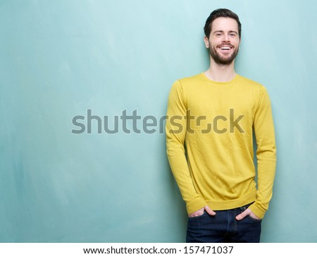 Portrait of a handsome young man smiling against blue background - stock photo