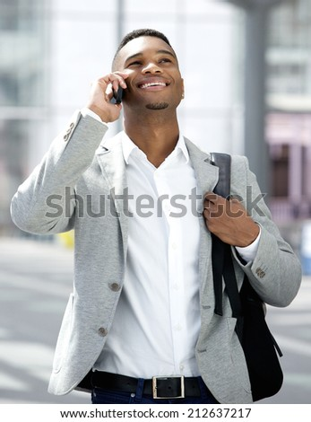 Portrait of a handsome young man walking and talking on mobile phone - stock photo