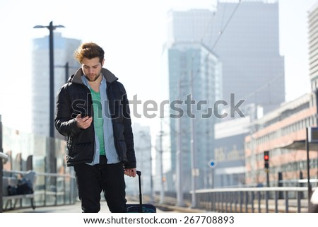 Portrait of a handsome young man walking with bag and mobile phone in the city - stock photo
