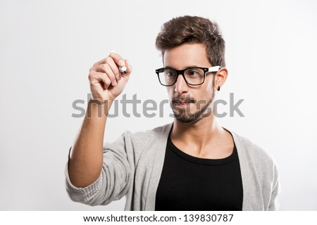 Portrait of a handsome young man wearing glasses and  writting something on a glass writeboard - stock photo