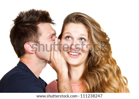 Portrait of a handsome young man whispering a secret to a cute woman against white - stock photo