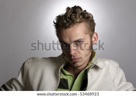 Portrait of a handsome young man with a white leather jacket. - stock photo