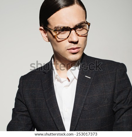 Portrait of a handsome young man with glasses and a suit in the studio on a white background, the concept of fashion - stock photo