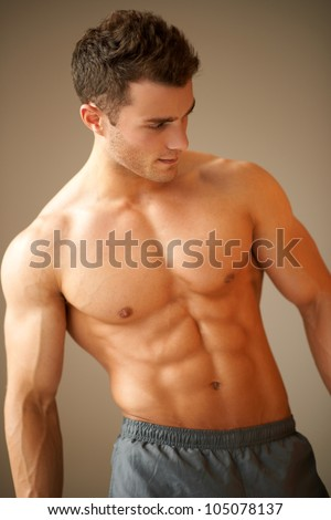 Portrait of a handsome young man with great physique posing on natural background - stock photo