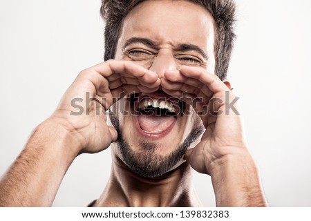 Portrait of a handsome young man yelling, over a gray background - stock photo