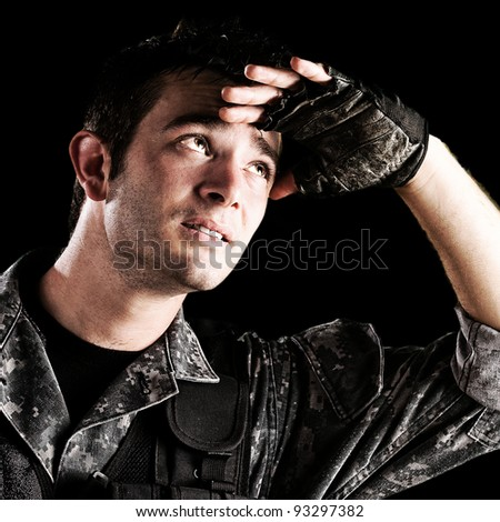 portrait of a handsome young soldier looking up against a black background - stock photo