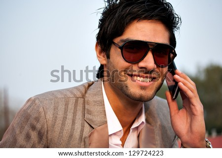 portrait of a handsome young talking on mobile phone in outdoor - stock photo