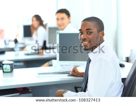Portrait of a happy African American entrepreneur displaying computer laptop in office - stock photo