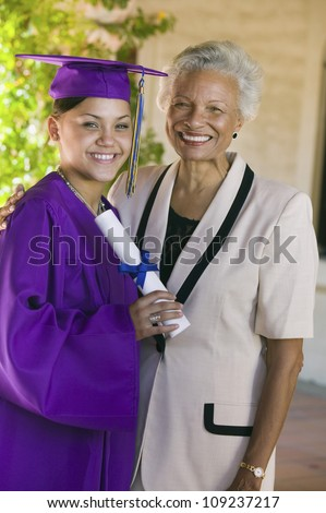 Portrait of a happy African American graduate with grandmother during graduation day - stock photo