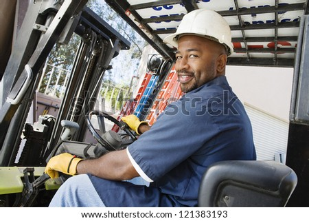 Portrait of a happy African American  male worker driving forklift at workplace - stock photo