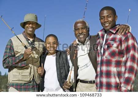 Portrait of a happy African family holding fishing rods - stock photo
