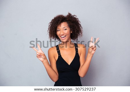 Portrait of a happy african woman showing victory with fingers over gray background and looking at camera - stock photo