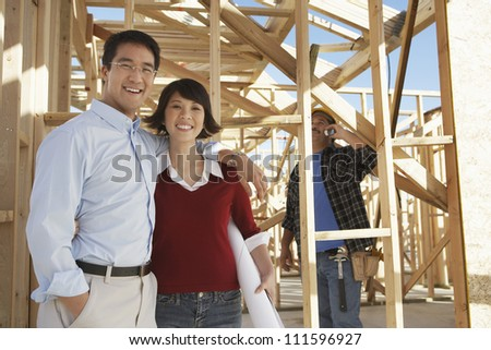 Portrait of a happy Asian couple at construction site with contractor in background - stock photo