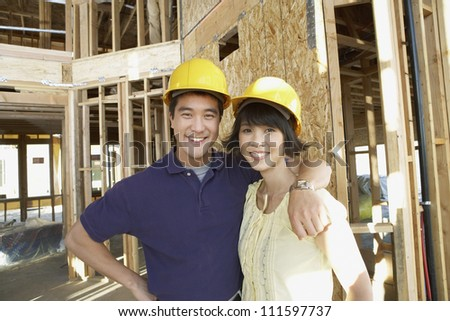 Portrait of a happy Asian couple wearing hard hats at construction site - stock photo