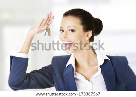 Portrait of a happy attractive caucasian businesswoman, real estate agent, holding a house key  - stock photo