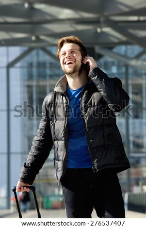 Portrait of a happy attractive man walking and talking on mobile phone - stock photo