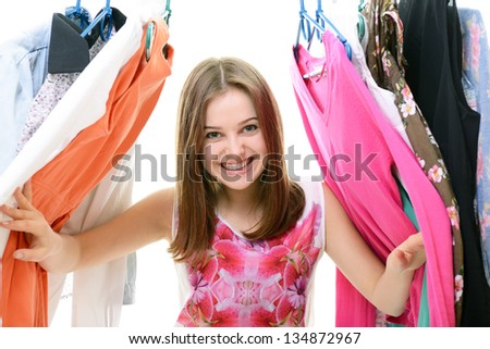 Portrait of a happy attractive teen girl making choices in wardrobe - stock photo